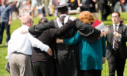 Family hugging graduate soon after Commencement